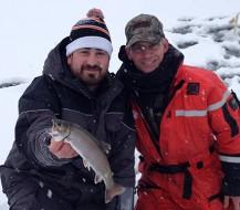 Deux homme montrant leur prise de truite en pêche blanche sur le Lac Témiscouata